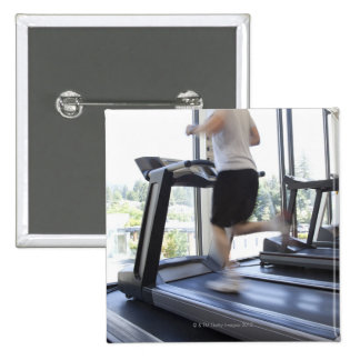 Young man running on a treadmill at health club, pinback button