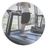 Young man running on a treadmill at health club, party plates