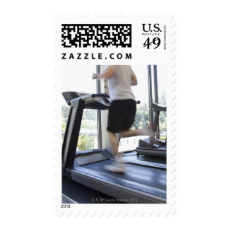 Young man running on a treadmill at health club, postage stamp