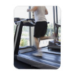 Young man running on a treadmill at health club, magnets
