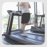 Young man running on a treadmill at health club, square sticker