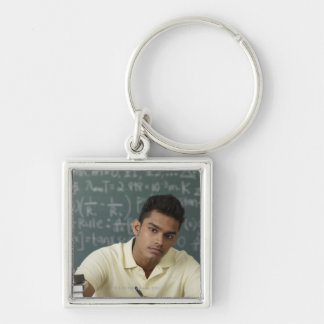 young man sitting at his desk, writing keychain