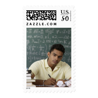 young man sitting at his desk, writing postage