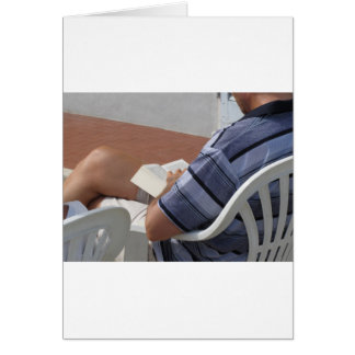 Young man sitting on chair reading book card