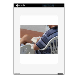 Young man sitting on chair reading book decal for iPad
