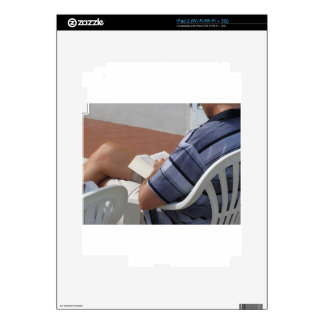 Young man sitting on chair reading book iPad 2 decal
