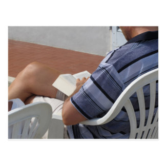 Young man sitting on chair reading book postcard