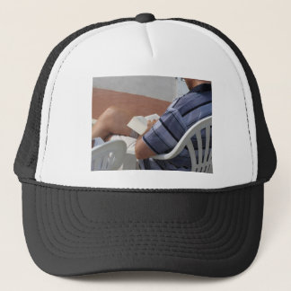 Young man sitting on chair reading book trucker hat