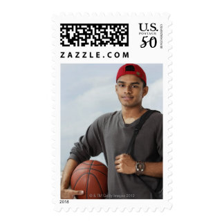 young man with red cap holding basket ball and postage