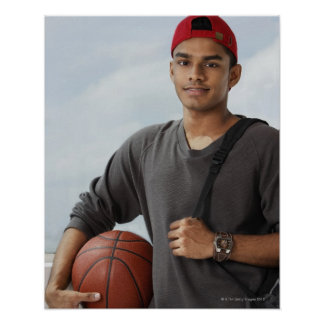 young man with red cap holding basket ball and poster