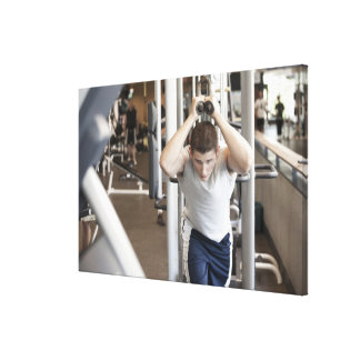 Young man working out his triceps on a cable canvas print