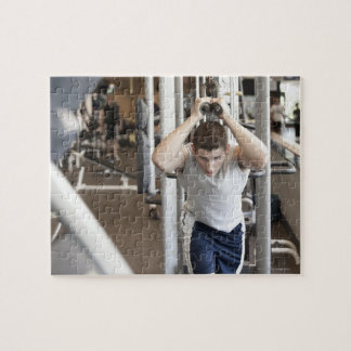 Young man working out his triceps on a cable jigsaw puzzle