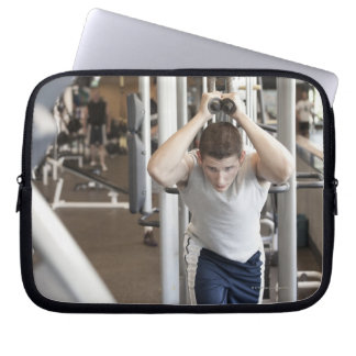 Young man working out his triceps on a cable laptop sleeve