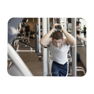 Young man working out his triceps on a cable magnet