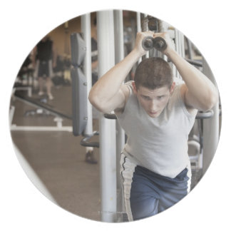 Young man working out his triceps on a cable plate