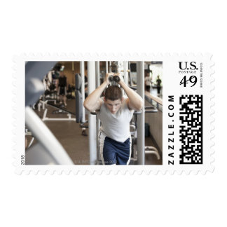 Young man working out his triceps on a cable postage