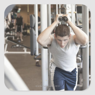 Young man working out his triceps on a cable square sticker