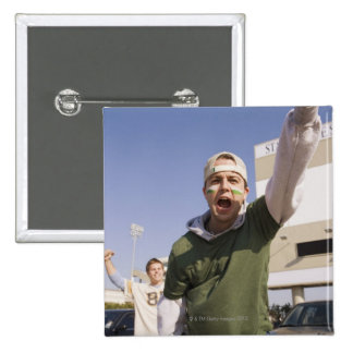 Young men cheering in parking lot before game 2 inch square button