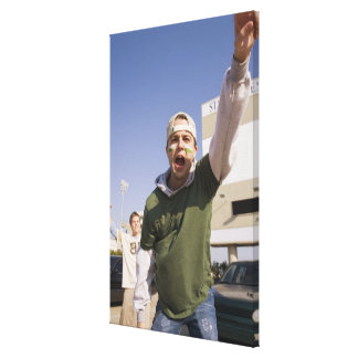 Young men cheering in parking lot before game canvas print