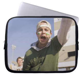 Young men cheering in parking lot before game laptop sleeves