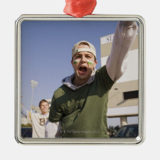 Young men cheering in parking lot before game metal ornament