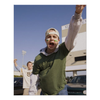 Young men cheering in parking lot before game poster
