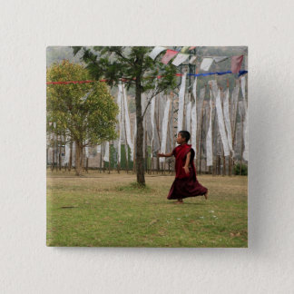 Young monk and prayer flags button