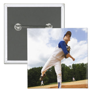 Young pitcher throwing baseball from mound buttons