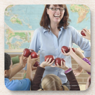 young students presenting apples to teacher coaster