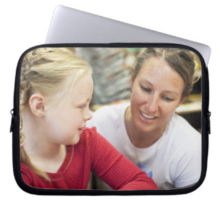 young teacher discussing homework w/ student laptop sleeve