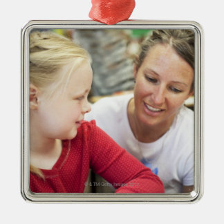 young teacher discussing homework w/ student metal ornament