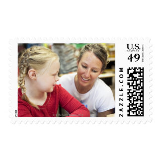 young teacher discussing homework w/ student stamps