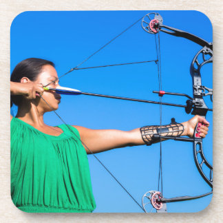 Young woman aiming arrow of compound bow coaster