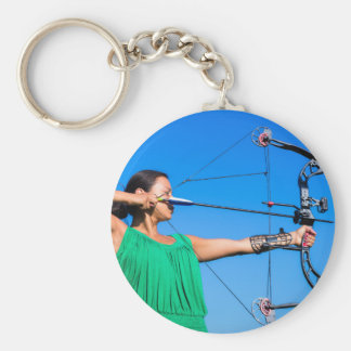 Young woman aiming arrow of compound bow keychain