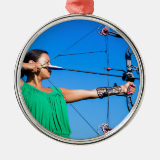 Young woman aiming arrow of compound bow metal ornament