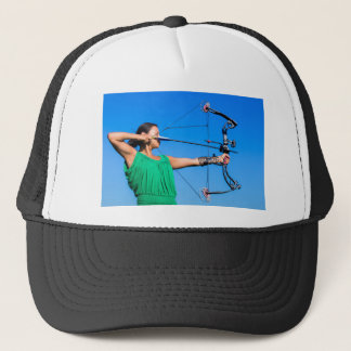 Young woman aiming arrow of compound bow trucker hat