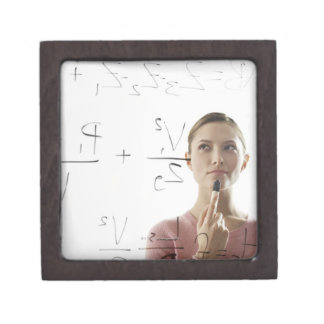 Young woman calculating equations on glass jewelry box
