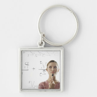 Young woman calculating equations on glass key chain