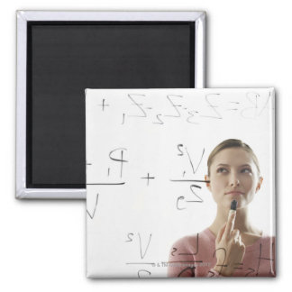Young woman calculating equations on glass magnet