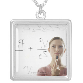 Young woman calculating equations on glass pendants
