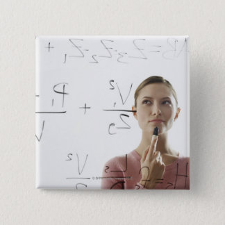 Young woman calculating equations on glass pinback button