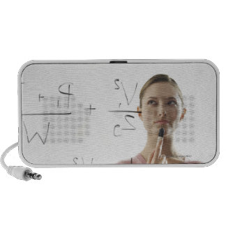 Young woman calculating equations on glass speakers