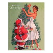 Young woman decorating Christmas tree with Santa Postcard