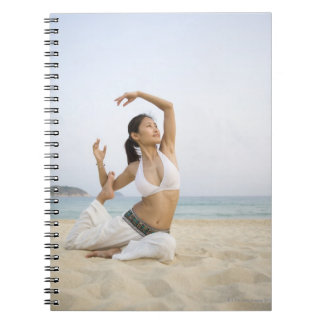 Young woman doing yoga on the beach spiral note book
