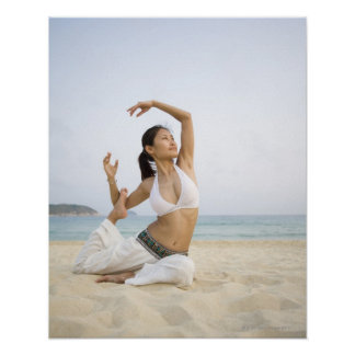 Young woman doing yoga on the beach poster