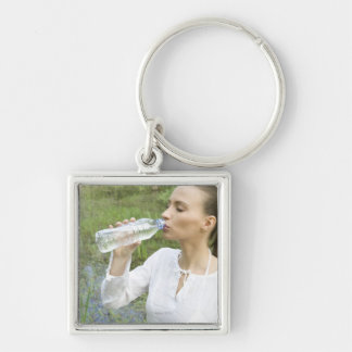 young woman drinking water from bottle keychain