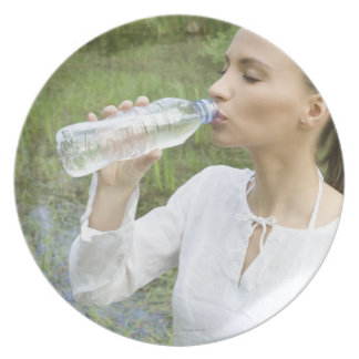 young woman drinking water from bottle melamine plate