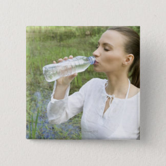 young woman drinking water from bottle pinback button