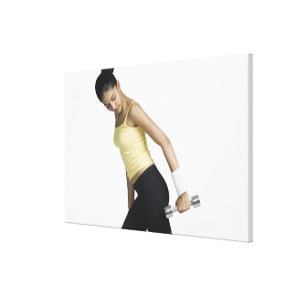 Young woman exercising with a dumbbell stretched canvas prints
