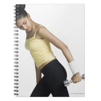 Young woman exercising with a dumbbell spiral notebooks